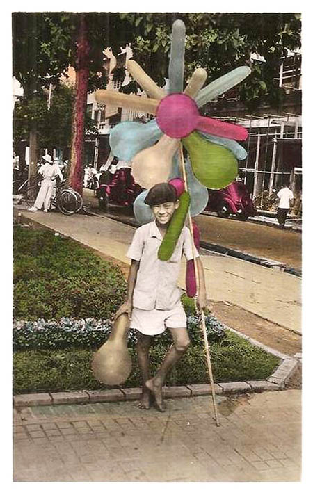 Một cậu bé bán bóng bay dạo trên phố Sài Gòn cười tươi, tạo dángtrước ống kính