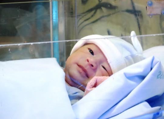 Cháu bé mỉm cười tinh nghịch với một điều dưỡng của khoa Hồi sức sơ sinh