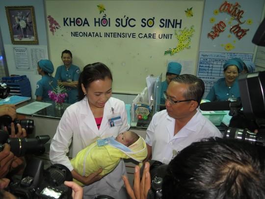 Bé sơ sinh được đưa ra gặp cha trong vòng tay của ThS-BS Phạm Thị Thanh Tâm, Trưởng khoa Hồi sức sơ sinh (phải) và TS-BS Nguyễn Thanh Hùng, Giám đốc BV Nhi Đồng 1