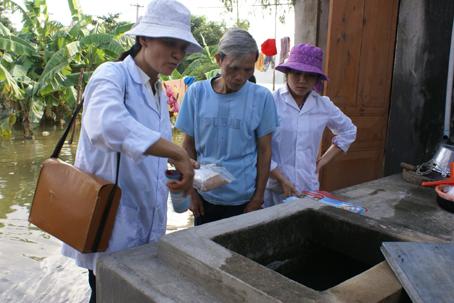 Cán bộ y tế hướng dẫn người dân cách xử lý nguồn nước sau mưa bão