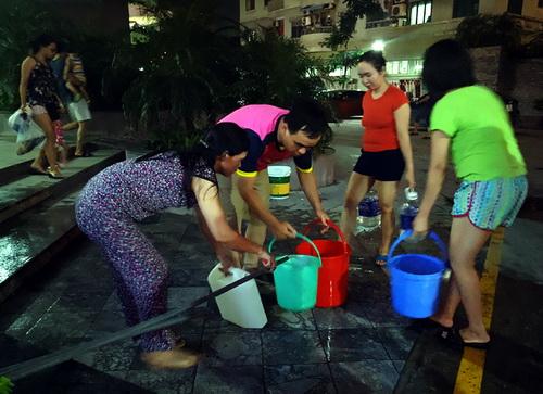 Chung cư mất nước, người dân xách từng xô nước về dùng.