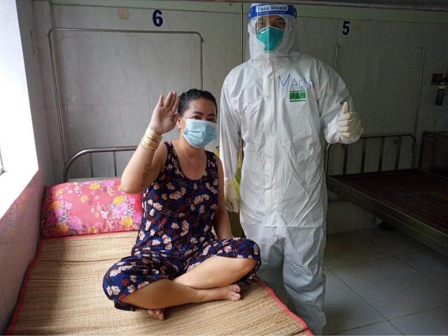 Điều dưỡng Nguyễn Văn Mạnh bên cạnh một bệnh nhân COVID-19 có chuyển biến tốt